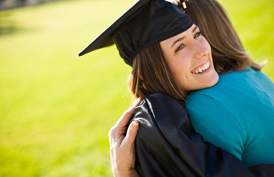 Female graduate hugging parent