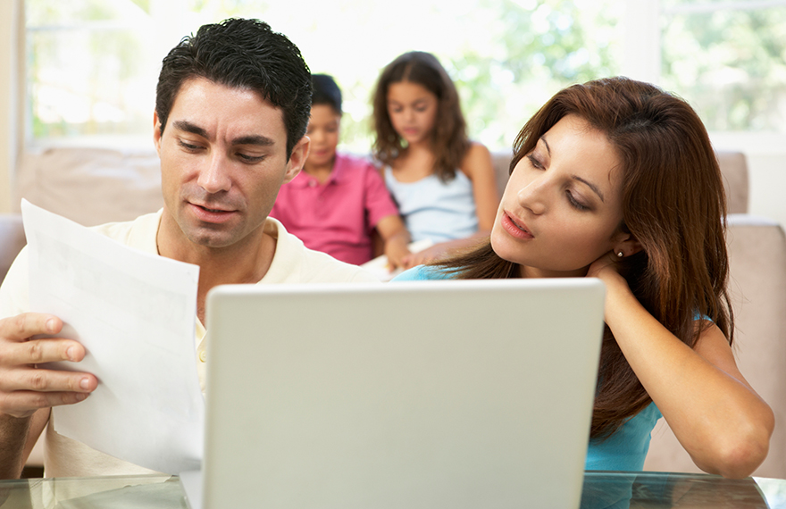 Parents talking at laptop, children in back