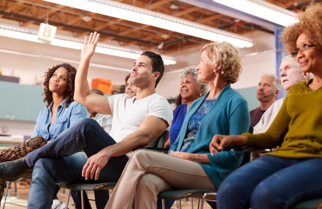 Man raising hand at community meeting