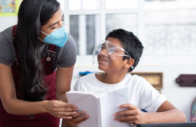 Teacher wearing mask helps student wearing face shield read